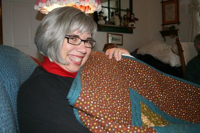 Excited Aunt Bet holding her new quilt