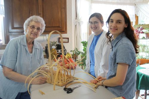 Granny, Sarah, and Hannah weaving a basket