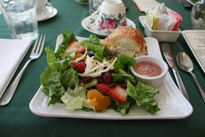 Fruit on a bed of greens and chicken salad croissant