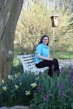 Sarah sitting by another birdhouse and lots of flowers