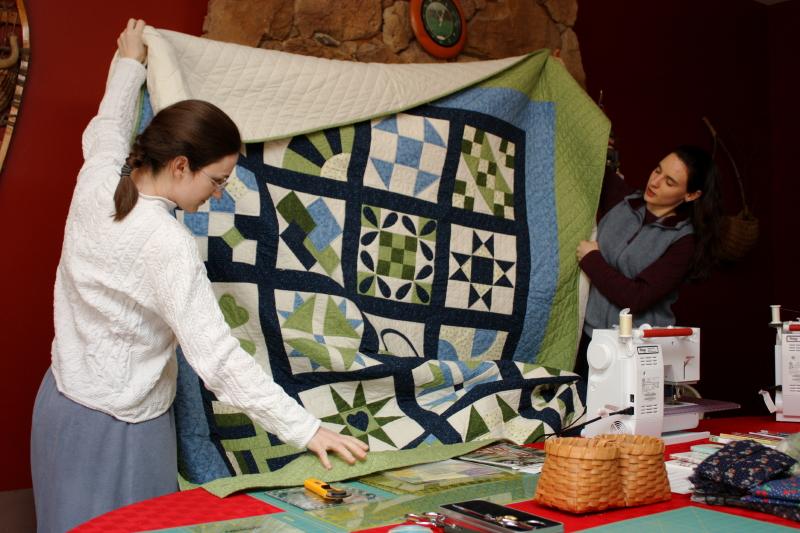 Sarah and Hannah displaying the sampler quilt
