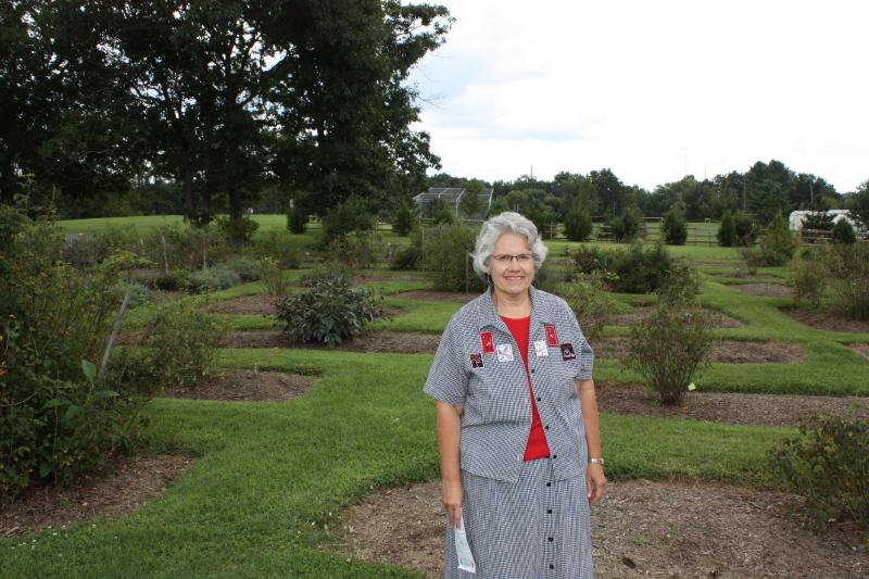 Deb standing in front of the heirloom rose garden