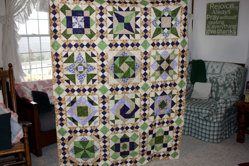 Sarah holding up a sampler quilt to be sent to the long-armer!