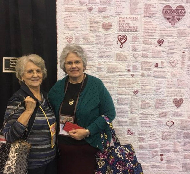 Mrs D and Deb in front of a cross-stitch quilt